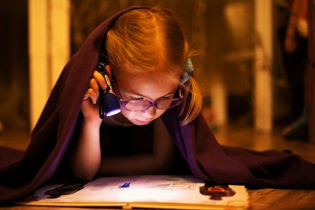 Little blonde girl 7 years old with glasses reading the book under the blanket with little flashlight at dark night time Premium Photo