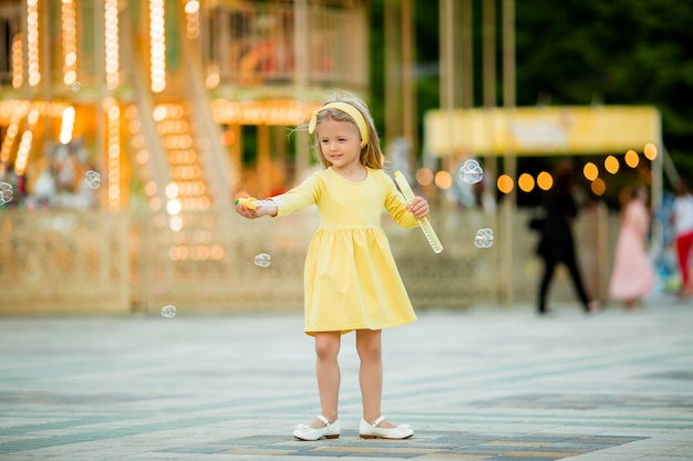 Little blonde girl in amusement park Premium Photo
