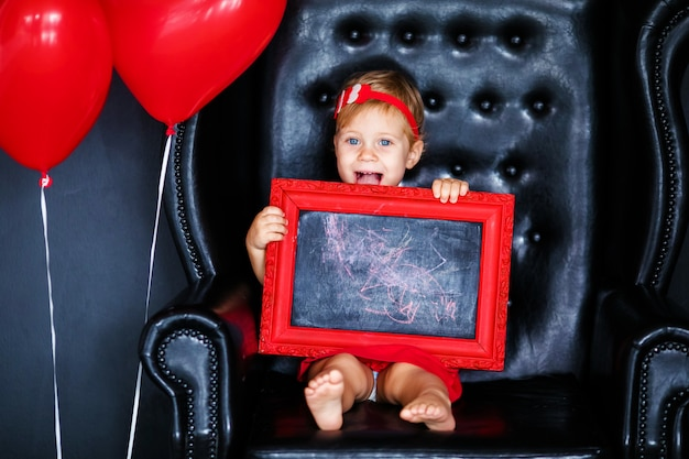 Little blonde girl in red dress with red wreath with hearts sitting on the armchair with red heart balloon on the st. valentine's day. Premium Photo