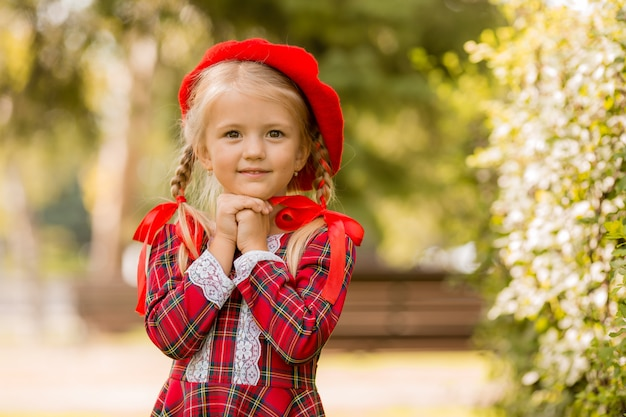 Little blonde girl in a red dress Premium Photo