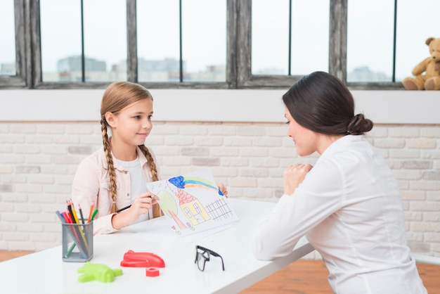 A little blonde girl showing drawn house on paper to her female psychologist Free Photo