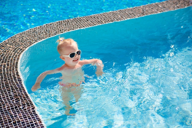 A little blonde girl splashing in the pool with clear water in the summer. Premium Photo