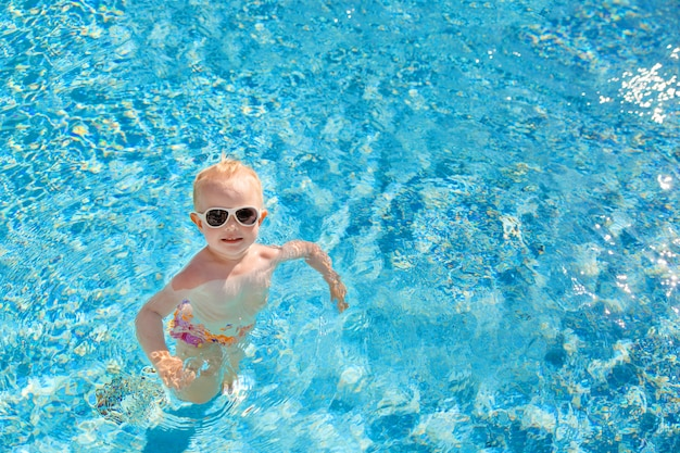 Little blonde girl swims in the pool with blue water Premium Photo