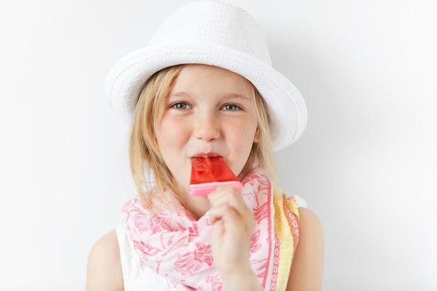 흰 모자를 쓰고 아이스크림을 먹는 금발 소녀 무료 사진