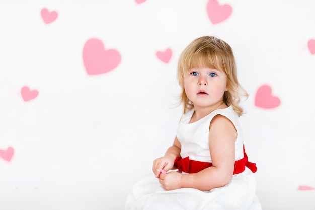 Little blonde girl in white dress with red ribbon on white floor with pink hearts on the  valentines day Premium Photo