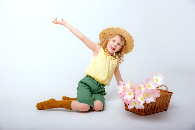 Little blonde girl with a basket of spring pink flowers Premium Photo