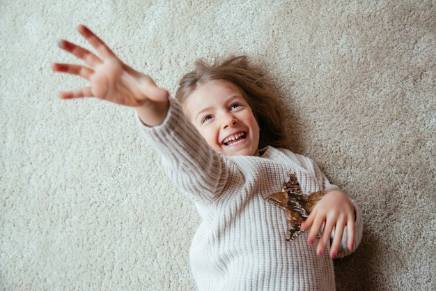 Little blonde kid on the floor with tickles Premium Photo
