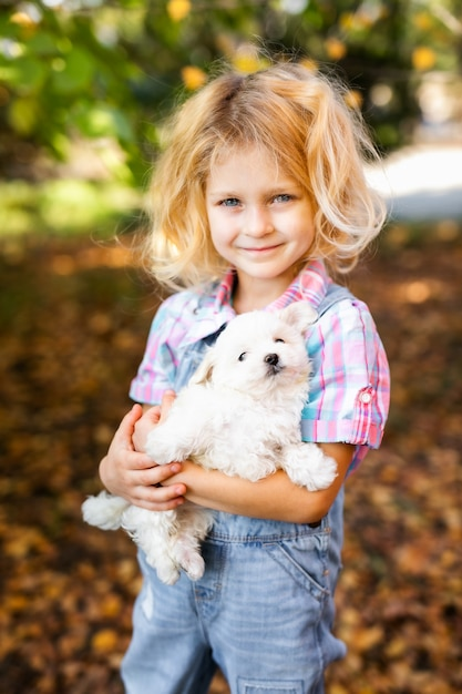 Маленькая белокурая малышка с двумя косами играет с красивым белым щенком Premium Фотографии