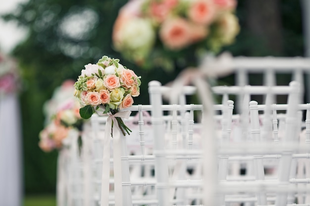 Little bouquets twined to the backs of white chairs Free Photo
