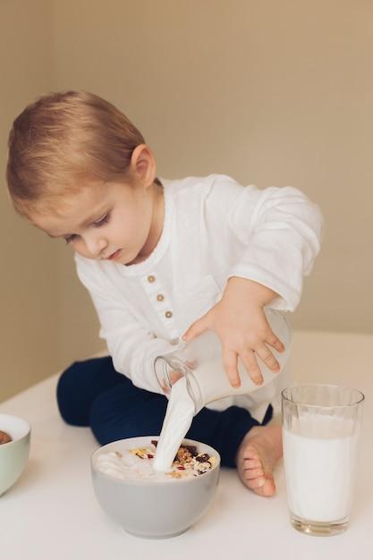 Little boy adding milk to cereals Free Photo