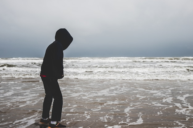 A little boy alone by the ocean Premium Photo