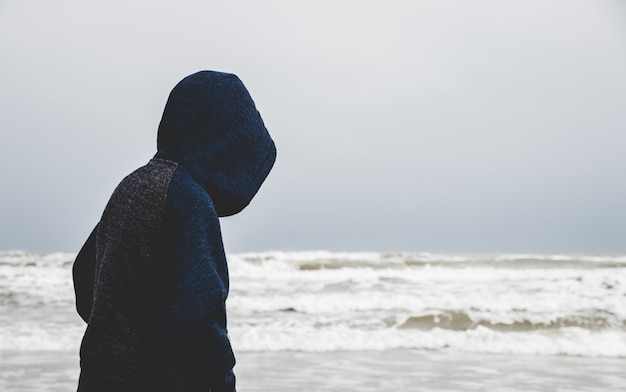A little boy alone by the ocean Premium Photo