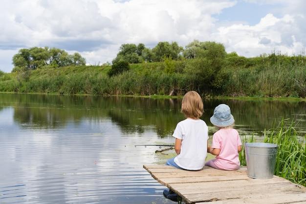 Маленький мальчик и девочка на рыбалке в пруду Premium Фотографии