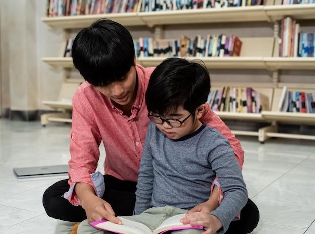 小さな男の子と先生が一緒に本を読んで、周りのぼやけた光 Premium写真