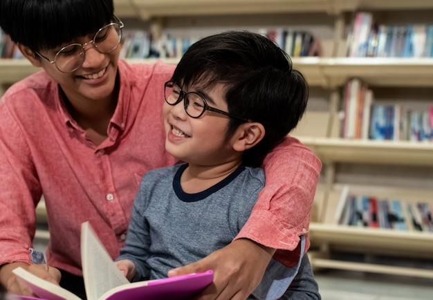 小さな男の子と先生が一緒に本を読んで、幸せな気持ちで、ぼやけた光 Premium写真
