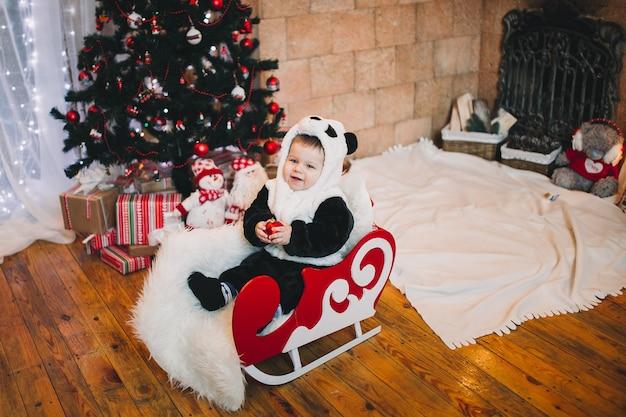 贈り物やプレゼントで飾られたクリスマスツリーの隣に座っている小さな男の子の赤ちゃん Premium写真