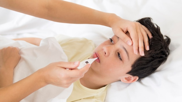 Little boy in bed having fever Premium Photo