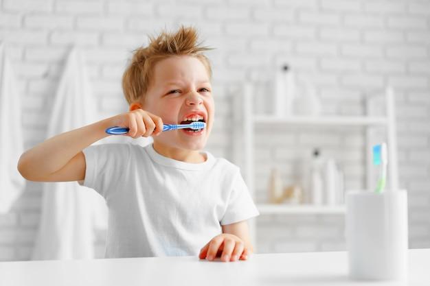 小さな男の子がバスルームで熱心に歯を磨く Premium写真