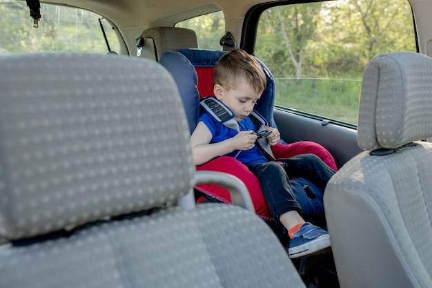 Little boy buckled up with seatbelt inside the car. vehicle and transportation concept. Premium Phot