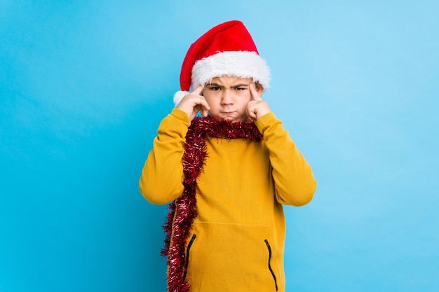 Little boy celebrating christmas day wearing a santa hat isolated focused on a task, keeping forefingers pointing head. Premium Photo