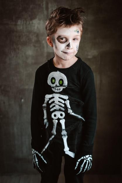 Маленький мальчик в костюме скелета, карнавал на хэллоуин в потрясающих декорациях, в атмосфере ужаса. Premium Фотографии