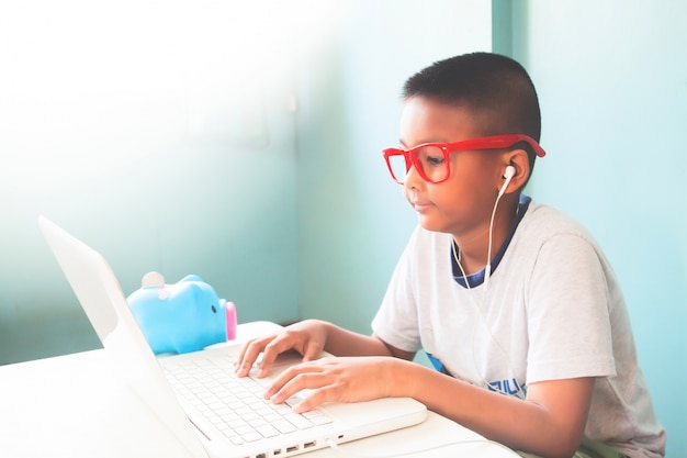 Little boy child wearing red glasses listening and using laptop computer Free Photo