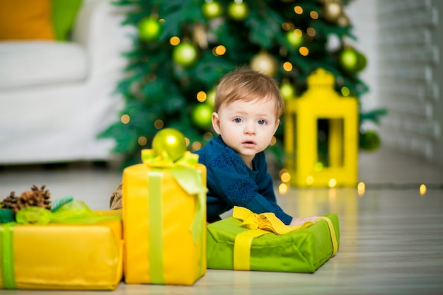 A little boy under the christmas tree lies, next to are christmas gift boxes. Premium Photo