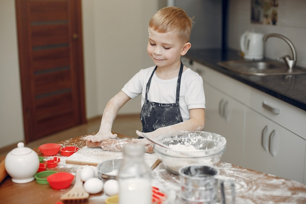 Little boy cook the dough for cookies Free Photo