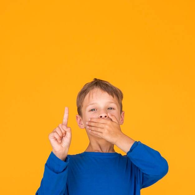 Little boy covering his mouth and pointing up Free Photo