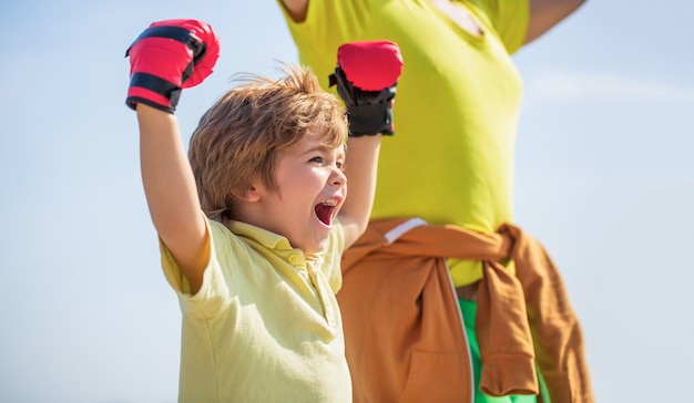 Little boy doing boxings exercise with grandfather. father is training his son boxing. little boy sportsman at boxing training with coach. sports man coaching boxing little boy in red boxing gloves. Premium Photo