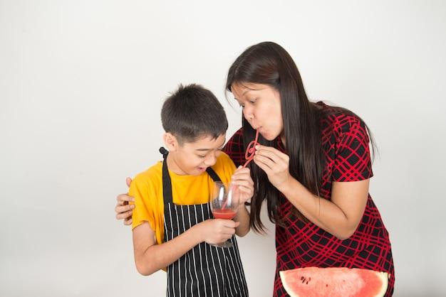 Little boy drink fruit juice watermelon with mother Premium Photo