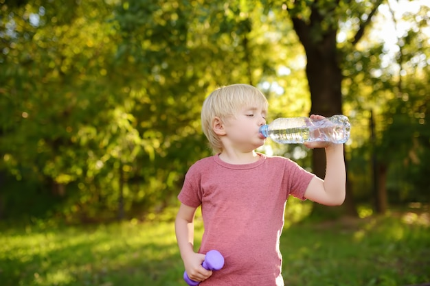 Little boy drinking water during workout with dumbbells Premium Photo