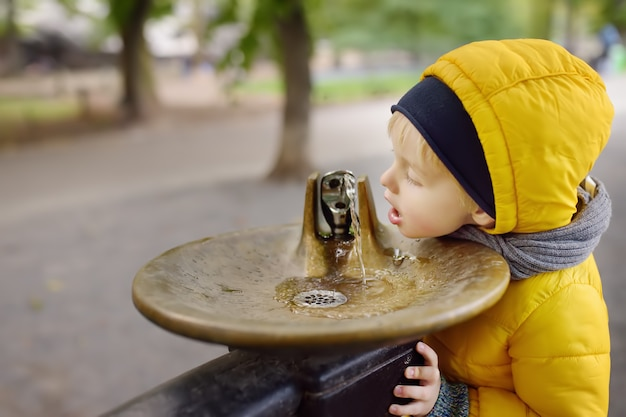 Little boy drinking water from city fountain during walking in central park Premium Photo