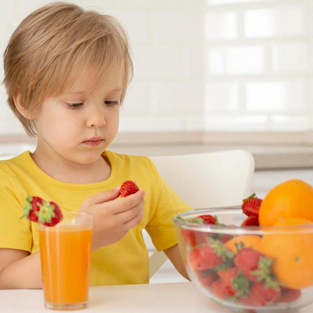 Ragazzino che mangia frutta Foto Gratuite