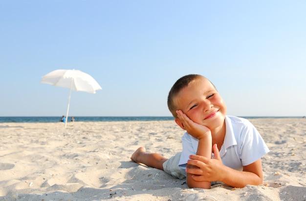 ビーチで楽しんでいる小さな男の子 無料写真