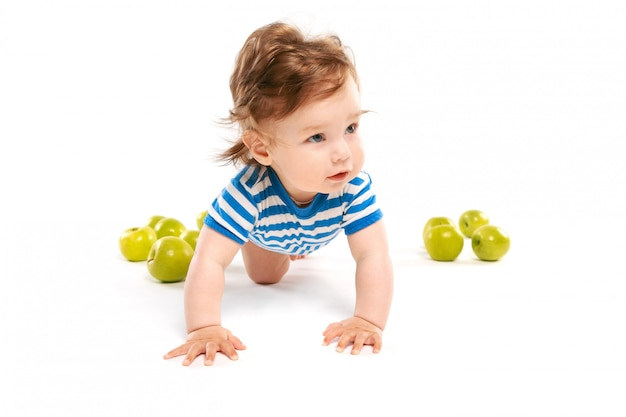 Little boy on the floor with green apples Premium Photo