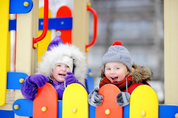 Little boy and girl in winter clothes having fun in outdoors playground Premium Photo