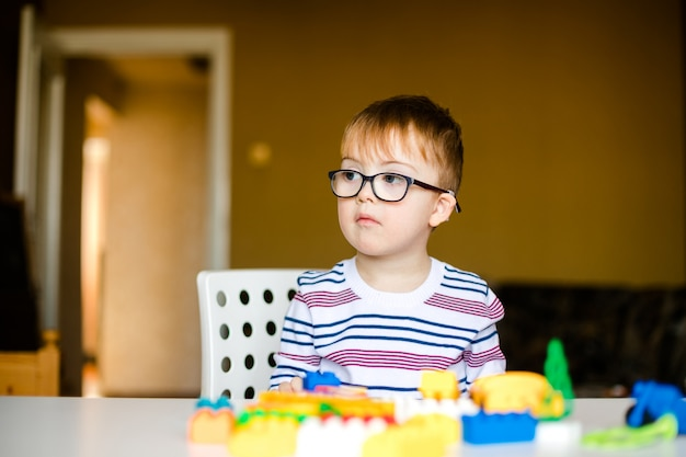 Little boy in the glasses with syndrome dawn playing with colorful bricks Premium Photo