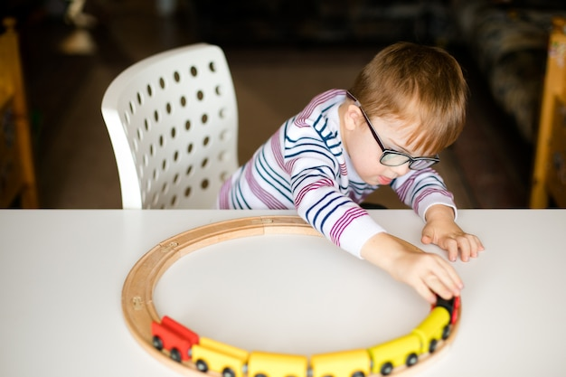 Little boy in the glasses with syndrome dawn playing with wooden railways Premium Photo