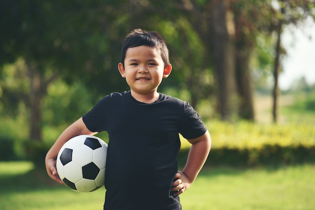 Little boy hand holding soccer football Free Photo