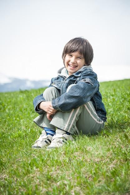 牧歌的なアルプスの美しい春の休暇を持つ小さな男の子 Premium写真