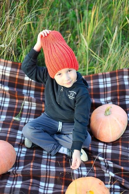 Маленький мальчик веселится во время экскурсии по тыквенной ферме осенью Premium Фотографии