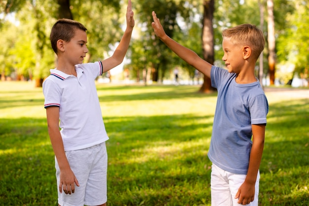 Little boy high fiving in the park Free Photo