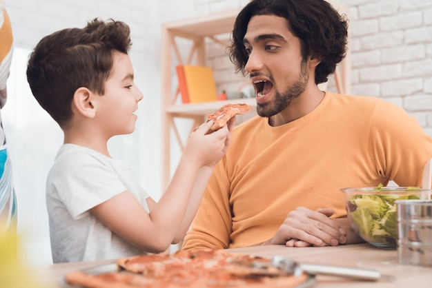 A little boy and his arab father eat pizza together. Premium Photo
