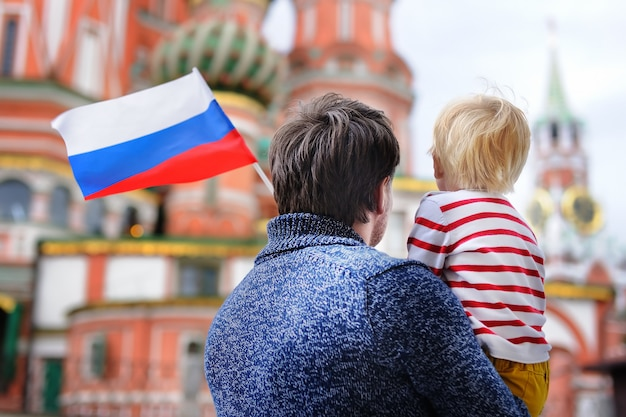 Little boy and his middle age father holding russian flag with saint basil's cathedral Premium Photo