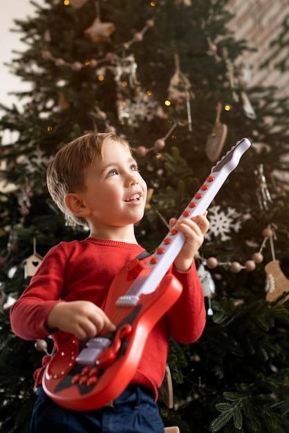 Маленький мальчик держит гитару рядом с деревом Бесплатные Фотографии