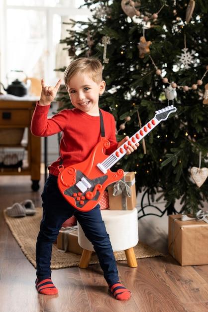 Маленький мальчик держит гитару Бесплатные Фотографии