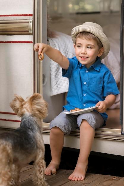 かわいい犬の横にあるプレートを保持している小さな男の子 無料写真