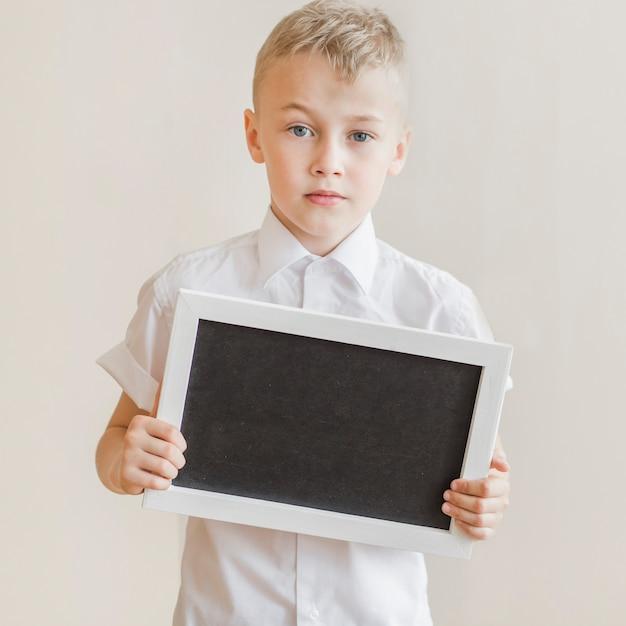 Little boy holding blackboard in studio Free Photo