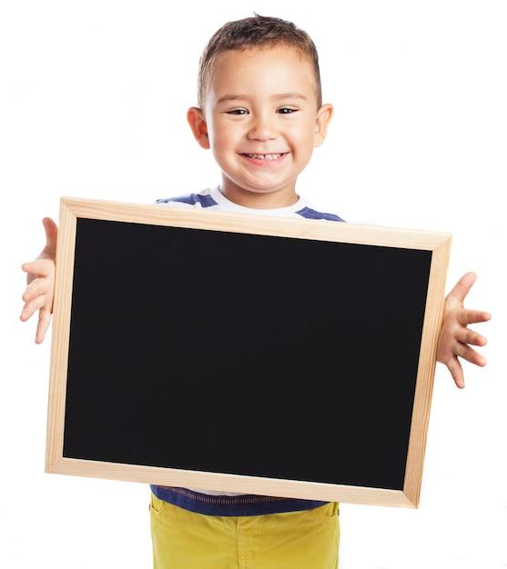 Little boy holding a blackboard Free Photo